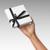 Scatola bianca del presente di festa della tenuta della mano della donna con il nastro del nero scuro Immagine Stock