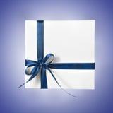 Scatola bianca isolata del presente di festa con il nastro blu su un fondo di pendenza Immagini Stock