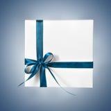Scatola bianca isolata del presente di festa con il nastro blu su un fondo di pendenza Fotografia Stock