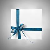 Scatola bianca isolata del presente di festa con il nastro blu un fondo di pendenza Fotografia Stock