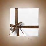 Scatola bianca isolata del presente di festa con il nastro di giallo arancio di Brown su un fondo di pendenza Fotografia Stock Libera da Diritti