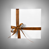 Scatola bianca isolata del presente di festa con il nastro di giallo arancio di Brown su un fondo di pendenza Immagini Stock Libere da Diritti