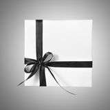 Scatola bianca isolata del presente di festa con il nastro nero su un fondo di pendenza Fotografia Stock Libera da Diritti
