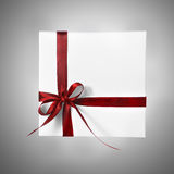 Scatola bianca isolata del presente di festa con il nastro rosso su un fondo di pendenza Fotografia Stock