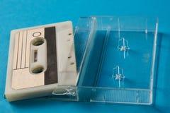 Scatola in bianco del nastro a cassetta con la retro cassetta su fondo blu Immagine Stock Libera da Diritti