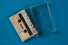 Scatola in bianco del nastro a cassetta con la retro cassetta su fondo blu Fotografie Stock