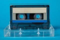Scatola in bianco del nastro a cassetta con la retro cassetta su fondo blu Immagini Stock Libere da Diritti