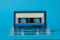 Scatola in bianco del nastro a cassetta con la retro cassetta su fondo blu Fotografia Stock Libera da Diritti