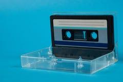 Scatola in bianco del nastro a cassetta con la retro cassetta su fondo blu Immagini Stock
