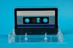 Scatola in bianco del nastro a cassetta con la retro cassetta su fondo blu Immagine Stock