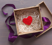 Scatola celebratoria con un cuore di lana rosso come regalo Fotografia Stock
