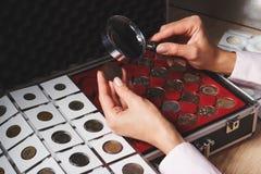 Scatola con le monete raccoglibili nelle cellule Fotografie Stock