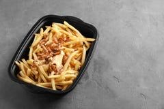 Scatola con le patate fritte, il bacon ed il formaggio immagine stock
