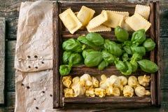 Scatola dei ravioli e del basilico della pasta Immagini Stock