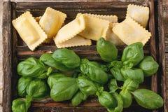 Scatola dei ravioli e del basilico della pasta Fotografia Stock