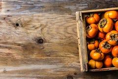 Scatola del cachi del cachi di frutta fresca su fondo di legno Copi lo spazio Immagine Stock Libera da Diritti