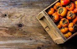 Scatola del cachi del cachi di frutta fresca su fondo di legno Copi lo spazio Fotografie Stock