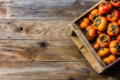 Scatola del cachi del cachi di frutta fresca su fondo di legno Copi lo spazio Fotografia Stock Libera da Diritti