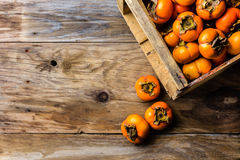 Scatola del cachi del cachi di frutta fresca su fondo di legno Copi lo spazio Immagine Stock