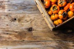 Scatola del cachi del cachi di frutta fresca su fondo di legno Copi lo spazio Fotografia Stock