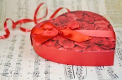 Scatola del cuore di cioccolato sopra le note classiche di musica Immagine Stock