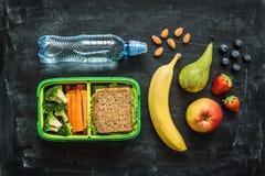 Scatola della refezione con il panino, le verdure, acqua e la frutta Fotografia Stock