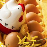 Scatola delle uova del cartone con le uova ed il temporizzatore Immagini Stock Libere da Diritti