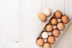 Scatola delle uova del cartone sulla tavola di legno Immagini Stock Libere da Diritti