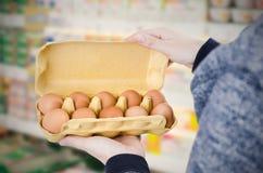 Scatola delle uova della tenuta dell'uomo in supermercato Immagini Stock