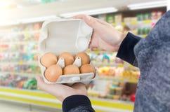 Scatola delle uova della tenuta dell'uomo in supermercato Fotografie Stock