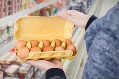 Scatola delle uova della tenuta dell'uomo in supermercato Fotografie Stock Libere da Diritti