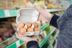Scatola delle uova della tenuta dell'uomo in supermercato Fotografia Stock Libera da Diritti