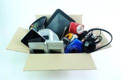 Scatola di carta con gli aggeggi utilizzati nocivi o vecchi di elettronica per uso quotidiano su fondo bianco fotografia stock