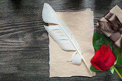 Scatola di carta d'annata del presente della rosa rossa della piuma sul holid del bordo di legno Fotografie Stock Libere da Diritti