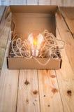 Scatola di carta marrone aperta con la lampadina accesa Fotografie Stock