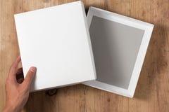 Scatola di cartone aperta mano su fondo di legno Fotografia Stock
