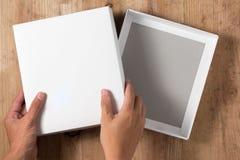 Scatola di cartone aperta mano su fondo di legno Fotografie Stock Libere da Diritti