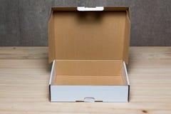 Scatola di cartone aperta su fondo di legno Immagini Stock