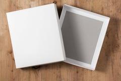 Scatola di cartone aperta su fondo di legno Fotografie Stock Libere da Diritti