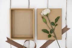 Scatola di cartone aperta su una tavola di legno immagini stock libere da diritti
