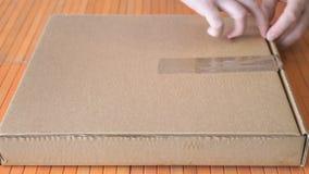 Scatola di cartone di apertura con una grande pizza video d archivio