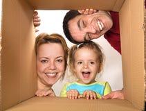 Scatola di cartone di apertura della famiglia fotografie stock libere da diritti