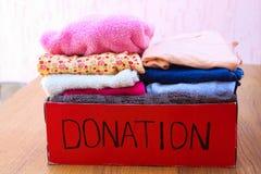 Scatola di donazione con i vestiti Una scatola di vestiti caldi Fotografia Stock Libera da Diritti