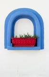 Scatola di finestra rossa nel telaio blu immagini stock
