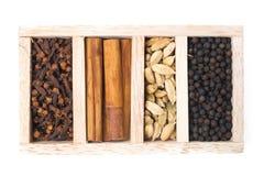 Scatola di legno con differenti generi di spezie, vista isolata e superiore Fotografia Stock