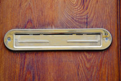 Scatola di lettera a porta chiusa dorata brillante sulle porte di legno immagine stock libera da diritti