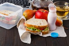 Scatola di pranzo con alimento e cancelleria deliziosi su backgroun di legno immagine stock