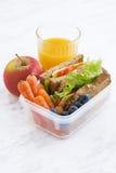 Scatola di pranzo con il panino di pane integrale, verticale Immagini Stock
