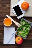 Scatola di pranzo con insalata, il taccuino ed il telefono Immagini Stock Libere da Diritti