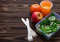 Scatola di pranzo con insalata, la mela, il mandarino ed il succo Fotografie Stock